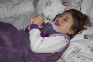 Leende Emily, her i en lilla fleece-nattpose fra Knotteklær